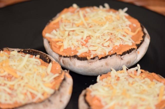 Rezepte: Kleinigkeiten: Portobello-Pizza, Portobellomit Paprika-Tomaten-Sauce gefüllt und mit Käse bestreut, ungebacken