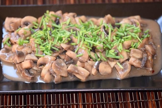 Rezepte: Beilagen: Sommerliches Pilzragout mit Schnittlauchröllchen garniert auf schwarzem Teller